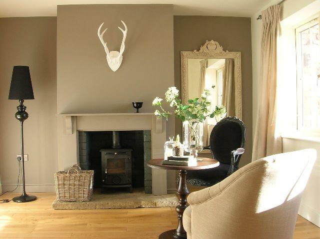 Snug with Farrow & Ball Charleston Grey accent wall. Chair by MADE.COM. Stove Aga