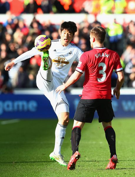 Ki Sung-Yueng controls the ball under pressure from Luke Shaw of Manchester United during the Barclays Premier League match between Swansea City and Manchester United at Liberty Stadium on February 21, 2015 in Swansea, Wales.