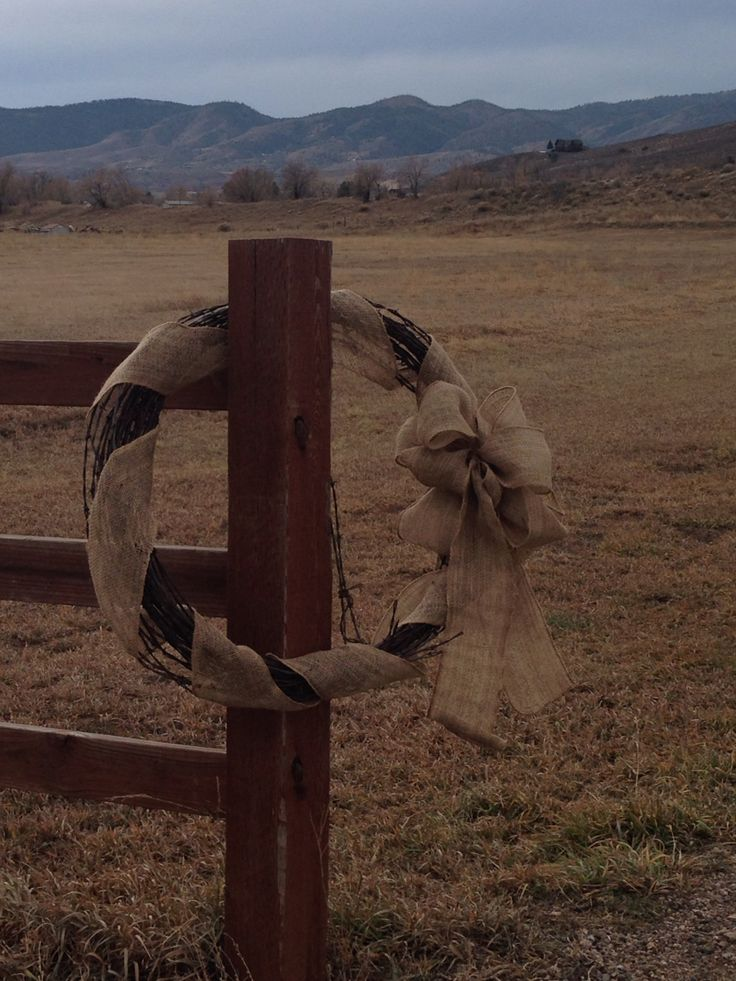 Burlap and Barbed Wire Wreath. It's on my fence at the entrance of my driveway!