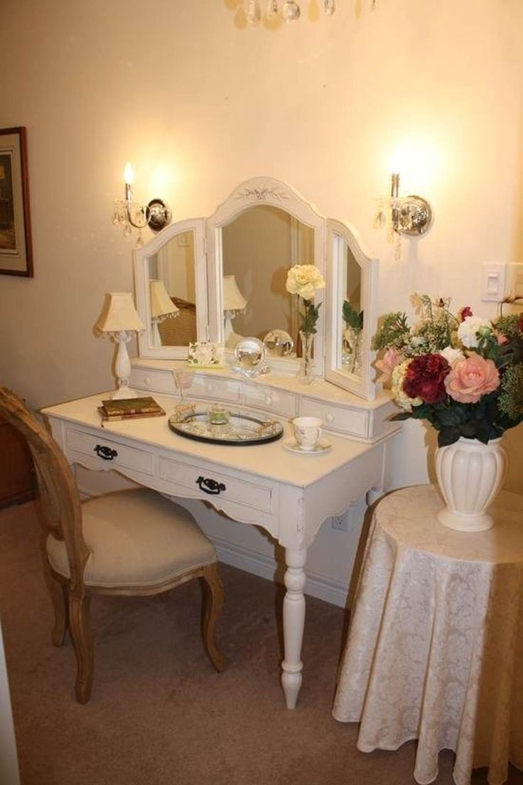 Simple White Small Wooden Antique Vanity Table Design With Elegant Chair On  Brown Floor As Well Beautiful Wall Lamp Beside Mirror Along With Flower… - Simple White Small Wooden Antique Vanity Table Design With Elegant
