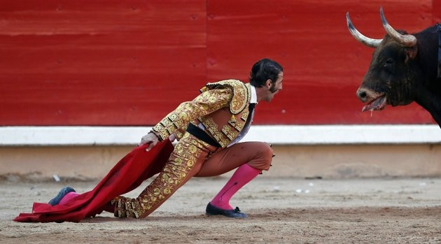 Spanish bullfighter Juan Jose Padilla kneels down in front of a bull during the last bullfight of the San Fermin festival in Pamplona July 14, 2012. Padilla lost an eye after getting gored last October during a bullfight in Zaragoza, northern Spain. He made a comeback five months afterwards. REUTERS/Susana Vera