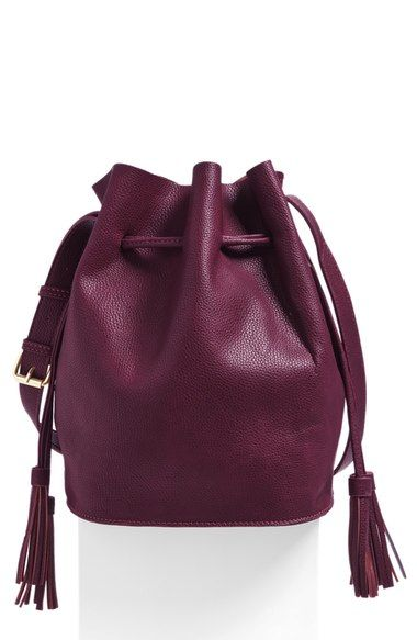 Chic tassels provide a bit of swish to a lavishly textured faux leather bucket bag finished with polished silvertone hardware.