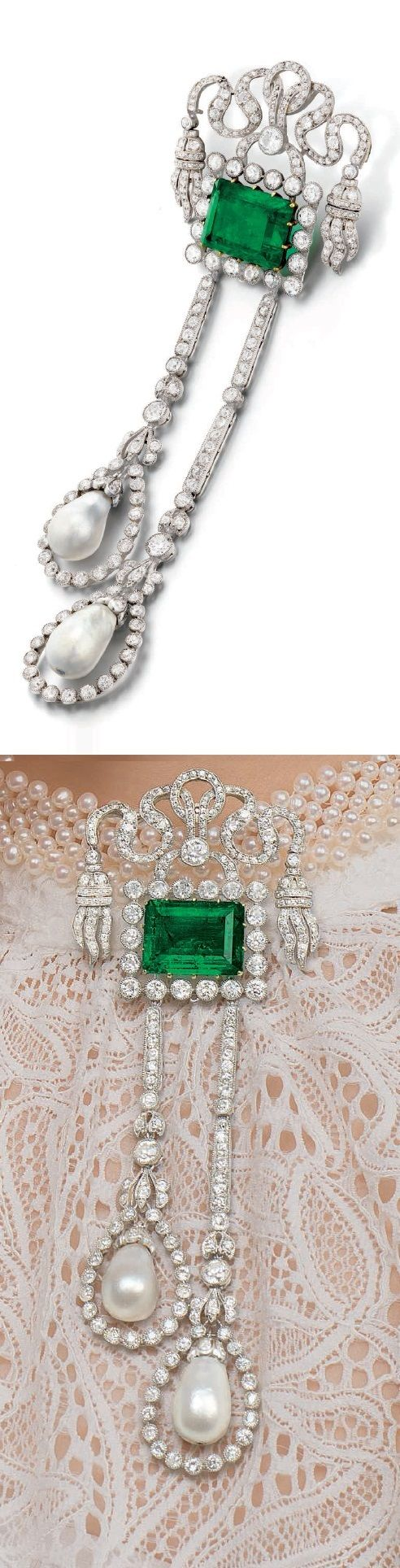 A Belle Epoque Platinum, 18K Yellow Gold, Emerald, Natural Pearl and Diamond Brooch, 1910. With a case signed Janesich, 18 Rue de la Paix, Paris, Monte Carlo. A fine example of a Belle Epoque jewel. The use of undulating ribbons, articulated tassels, natural pearl pendants, and millegrain-set diamonds centring upon an impressive emerald, is reminiscent of the naturalistic elegance of the period. A rare surviving example of what came to be known as the Golden Age of 20th C France