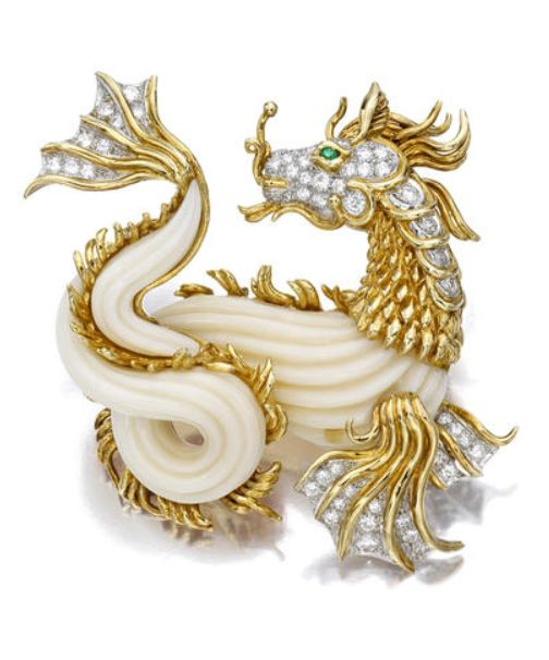 A coral, diamond and emerald brooch, Van Cleef & Arpels designed as a carved white coral and textured gold dragon, enhanced by pavé-set diamond detail and a circular-cut emerald eye; signed Van Cleef, no. NY 40551; estimated total diamond weight: 1.60 carats; mounted in eighteen karat gold and platinum.