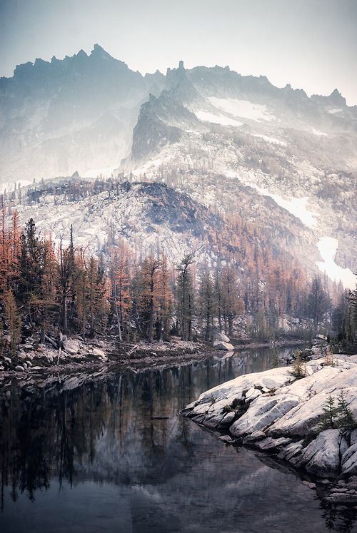 Snowy mountains and a river and autumn trees