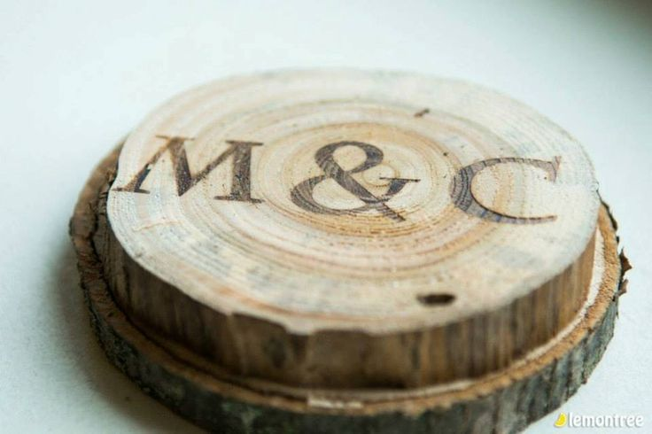The initials of the bride and groom etched into wood discs as part of the rustic theme for the centre pieces.