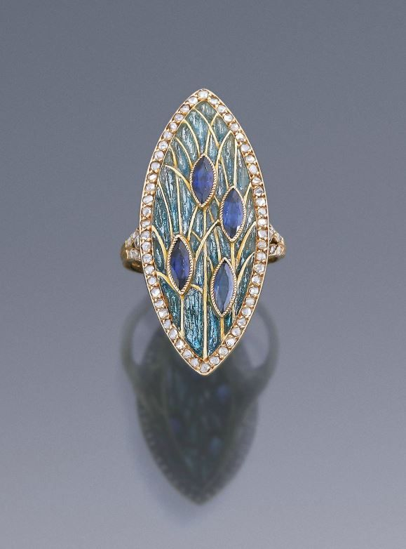 George Fouquet - This very unusual ring was designed and made by Georges Fouquet in Paris in 1908. The slender shank bears a slightly convex navette-shaped ornament edged with rose-cut diamonds. In the centre is a design of stylized ears of wheat; gold stalks form a framework for shining blue enamel. Date: 1908. Made in: Paris.
