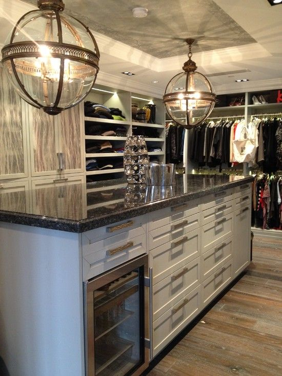 source: LA Closet Design      Restoration Hardware Victorian Hotel Pendant Bronze over huge closet island with black countertops. Faux bois wallpapered doors. white drawer storage and mini fridge. Weathered hardwood flooring and combination rack, shelf and cupboard storage.