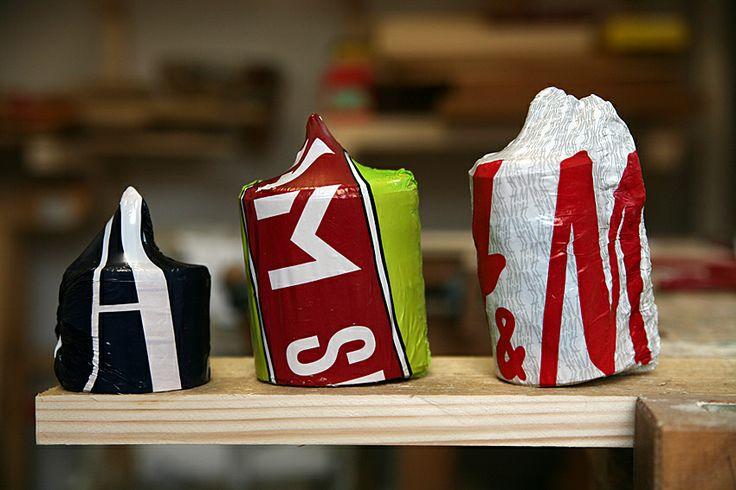 näverburkar inpackade i krympta plastpåser med loggar på.