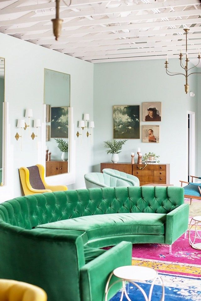 Vintage living space with light mint green walls, and a green velvet curved sofa