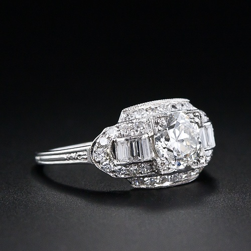A stunning, classic Art Deco diamond engagement ring in platinum from the 1920s featuring a bright white European-cut diamond weighing 1.02 carats. The diamond, which appears even larger due to its square setting, is flanked by a row of baguettes on each side and the multi-tiered mounting is framed with small sparkling single-cut diamonds which follow the geometric outline. Hand engraved detailing on the shoulders of the ring shank complete this timeless vintage engagement ring.