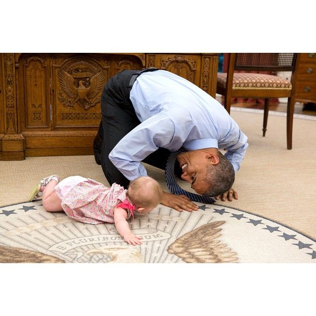 President Obama plays with Ella Harper Rhodes, daughter of Deputy National Security Advisor Ben Rhodes, in the Oval Office today.