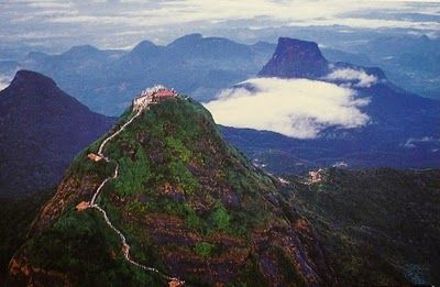 Adams Peak, Sri Lanka.  We hiked this at sunset, walked all night up step after step, got to the top, rang the bell, and sat down to watch the sunrise, from what felt like the top of the world. Amazing experience!
