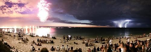 This was taken in Australia. Three separate things happening at once:On the left, fireworks exploded as part of Australia Day celebrations. In the middle, it's Comet McNaught. Then on the right, there's lightning from a thunderstorm far away.
