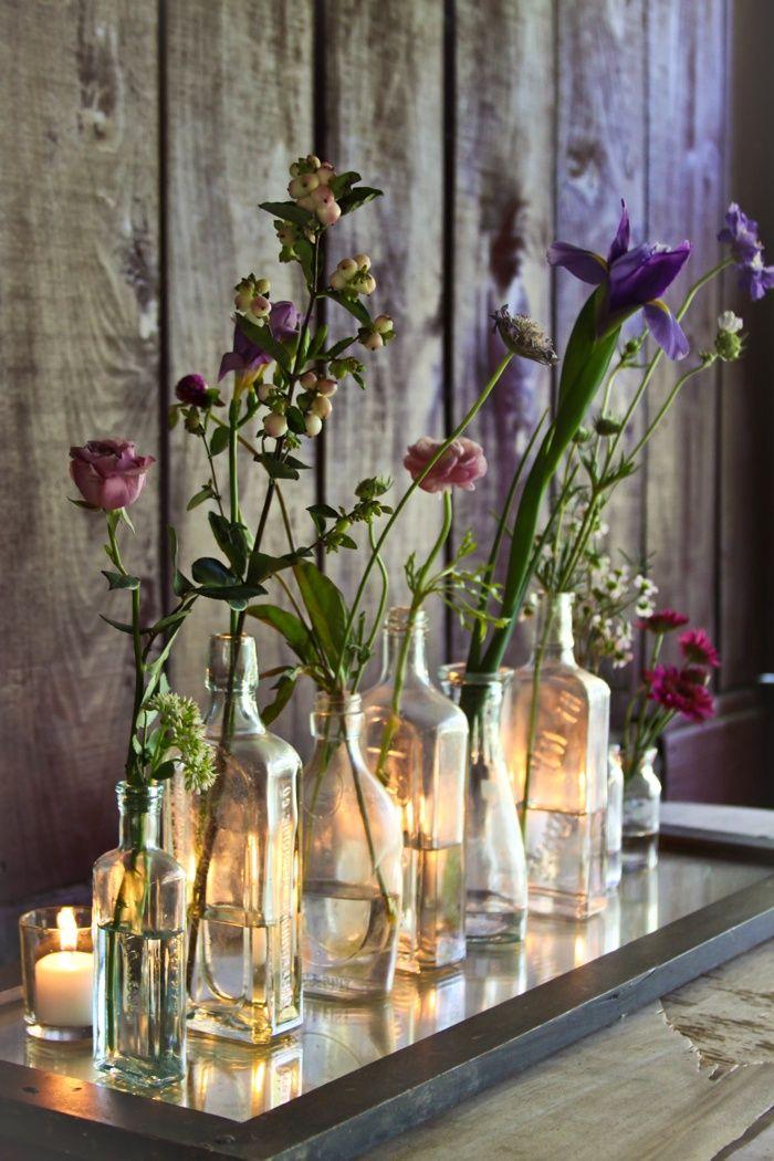 Floral arrangement in vintage bottles with tea-light candles behind