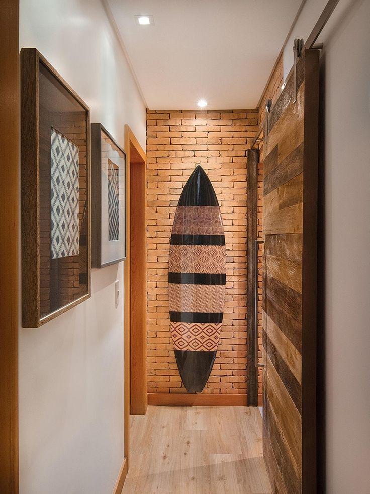 O destaque do corredor é a prancha posicionada sobre a parede revestida com tijolos rústicos, refletindo o gosto do casal por mar e surfe. A porta de correr foi feita de madeira de demolição e enfatiza a proposta rústica chique.