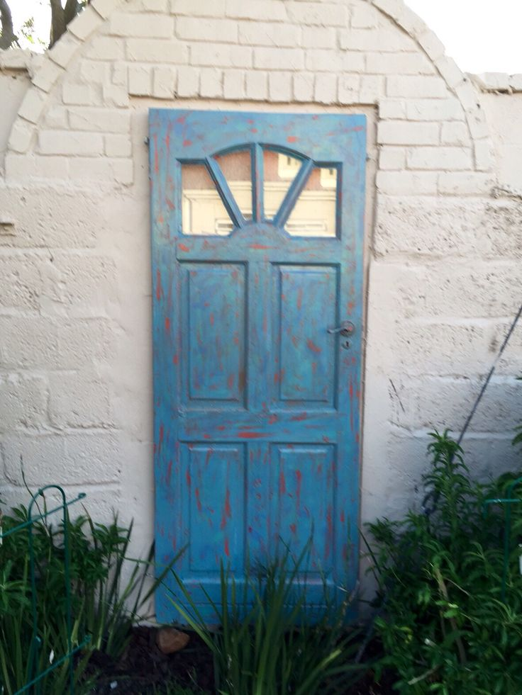 This old front door was given the chalk paint treatment and then hung in an interesting spot on a garden wall where a door or gate must of been in the past.