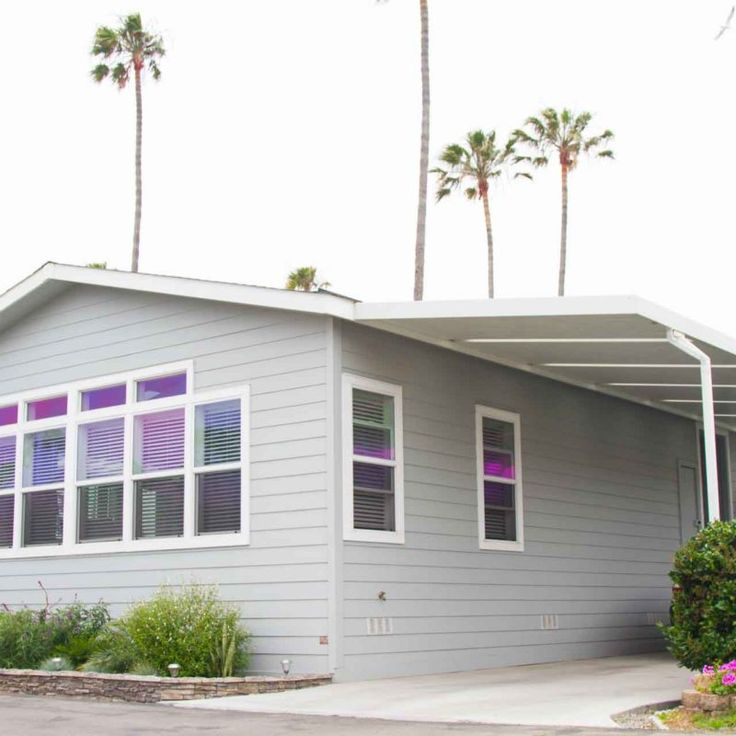 """This popular """"open concept"""" beach style cottage home has a white kitchen with stainless steel appliances over looking its large expansive great room that has been styled with lots of transom windows, skylights, and clerestories overhead."""