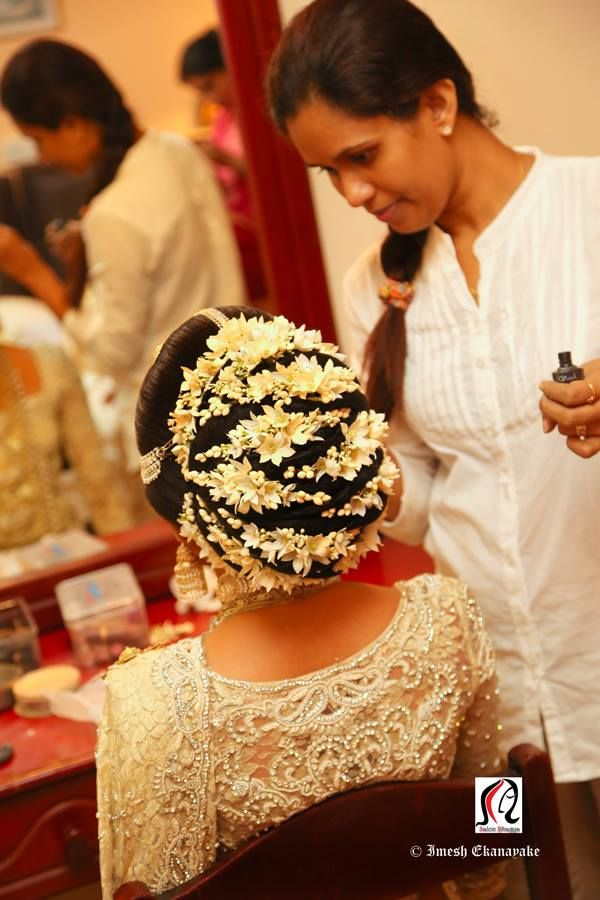 What a beautiful large low bun with real flower gajras! Care however should be taken before adopting such hairstyles, as due to it's high static charge, it will cause phlegm to move up in the throat, causing the voice to quaver & a frequent urge to clear the throat. A heavy chabi chhalla with a long & wide hook if inserted at the edge of the pleats of the saree, will reduce this problem as it's hook will activate the acupressure points that act to keep the throat clear.
