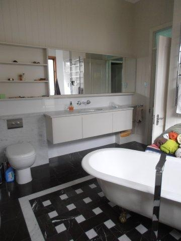 Queenslander. Bathroom renovation.    Marble tiling, freestanding bath tub & taps, custom cabinet work and hidden cistern make this bathroom a little special.  Original VJ wall cladding & 3.3 meter high ceilings highlights the beauty of this classic Queenslander.    www.empiredesigns.com.au