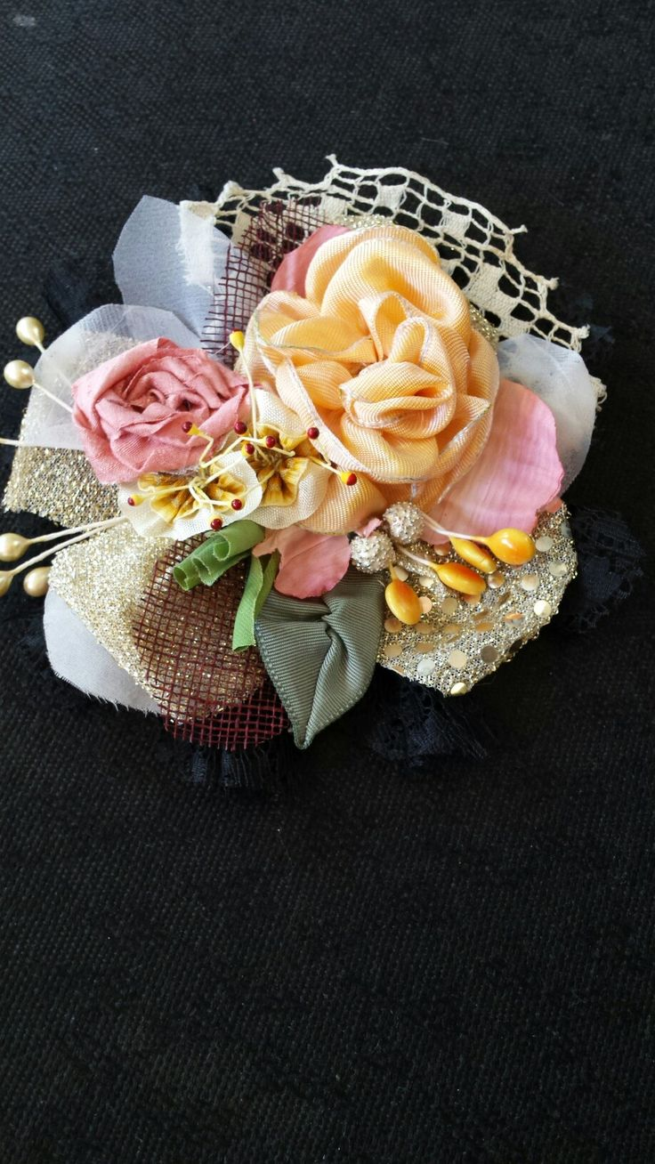 I see a lot of brooches made of flowers, using all kinds of materials. From denim, tweed, cotton or wool to silk. This one I made using vintage lace, ecru and black as background, and silk and rayon seam binding ribbon for the flowers. Vintage stamens all around. I love the yellow 'lollipop' stamens!
