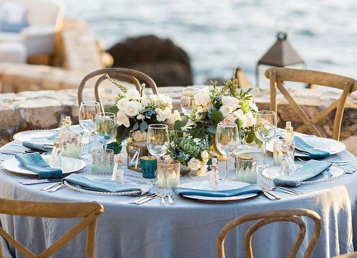 Round tables with mismatched chairs and sky blue tablecloths perfect for beach styling wedding by @brides •