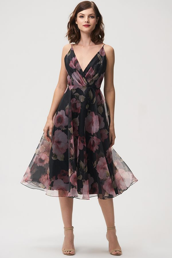 Jenny Yoo Bridesmaids, the floral printed Sabrina dress features a surplice bodice with delicate spaghetti straps for a feminine silhouette. The taffeta circle skirt hits at midi tea length and billows out to create movement. V Neck. This dress is fully lined with a center back seam. Perfect for a cocktail event, garden, or summer wedding.  Available in Black and Blush.