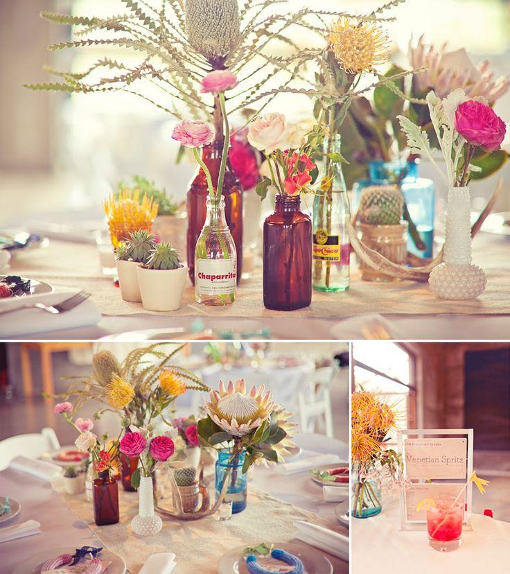 garrafas diversas usadas como vasos para flores.
