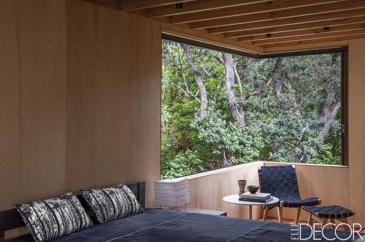 habitacion con persianas correderas y ventanas que se abren a los árboles; las paredes están fabricadas en contrachapado de #Alamo, y la silla y el otomano son diseños de #JensRisom.