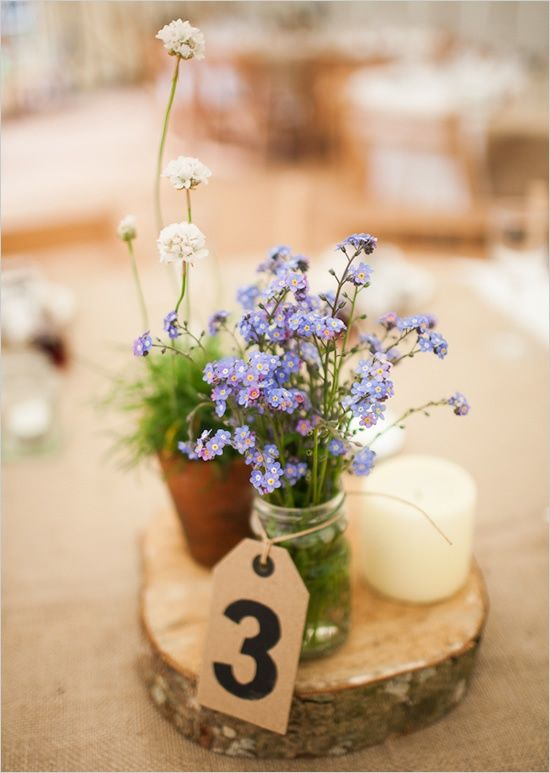 The perfect Mediterranean/Provençal numbered table centre  -  a small pot of herbs, some local country flowers, a candle or two (different sizes), and perhaps a bottle of olive oil with small dishes and bread for dipping and tasting .... plus some olives!