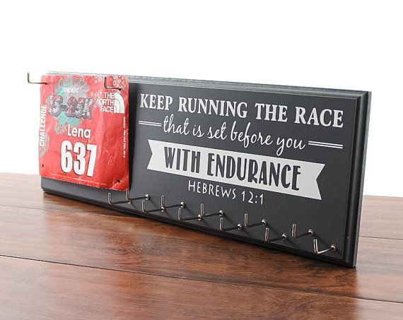 Running Medal Holder and Race Bib Display - Inspirational graphic Hebrews 12:1  This display is the perfect way to Strut Your Stuff for all to see. Runners can express their faith with this inspirational quote and display their medals of achievement. Our displays are handmade with the end result being a work of art that anyone would be proud to hang on their wall.  Creating this display is done in numerous steps. We begin with routing, sanding, drilling and priming. Then we paint with high…