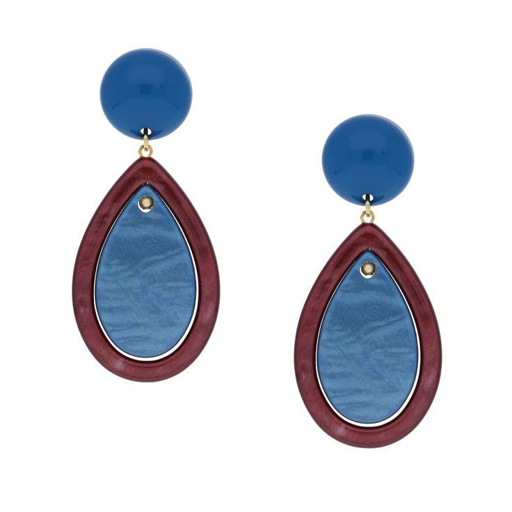 Einen maritimen Touch hat der Ohrring Vedella mit Clip in Blau und zartem Rot. Das angenehme Blau des runden Steins am Clip spiegelt sich im tropfenförmigen Element darunter wieder. Die hellrote Mitte des Tropfens schimmert durch ihre senkrechte Oberflächenstruktur aus jedem Blickwinkel anders und macht den Ohrring zum Blickfang. Ein Hingucker für den Alltag!