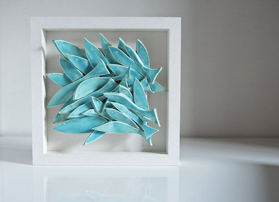 please note that the arrangement of fish varies from tile to tile, the photos represent the general design and colour finish .....................  school of fish, unique framed 3D ceramic artwork  sculptured entirely by hand, where every single fish is cut, smoothed and individually arranged on a tile, glazed in beautiful turquoise blue   the art tile comes in a simple white wooden frame; there is no glass fitted to bring out the the sculptural, textural, 3D qualities of the artwork; the…