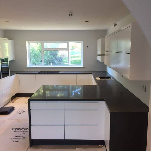 This beautiful white glossy kitchen features the dark grey Grigio Scuro Pura. The white and black combination in this kitchen adds a modern style to the hub of the home.