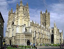 View of the exterior of Canterbury Cathedral on a bright day. The building is of pale stone with three large towers and much ornate Gothic d...