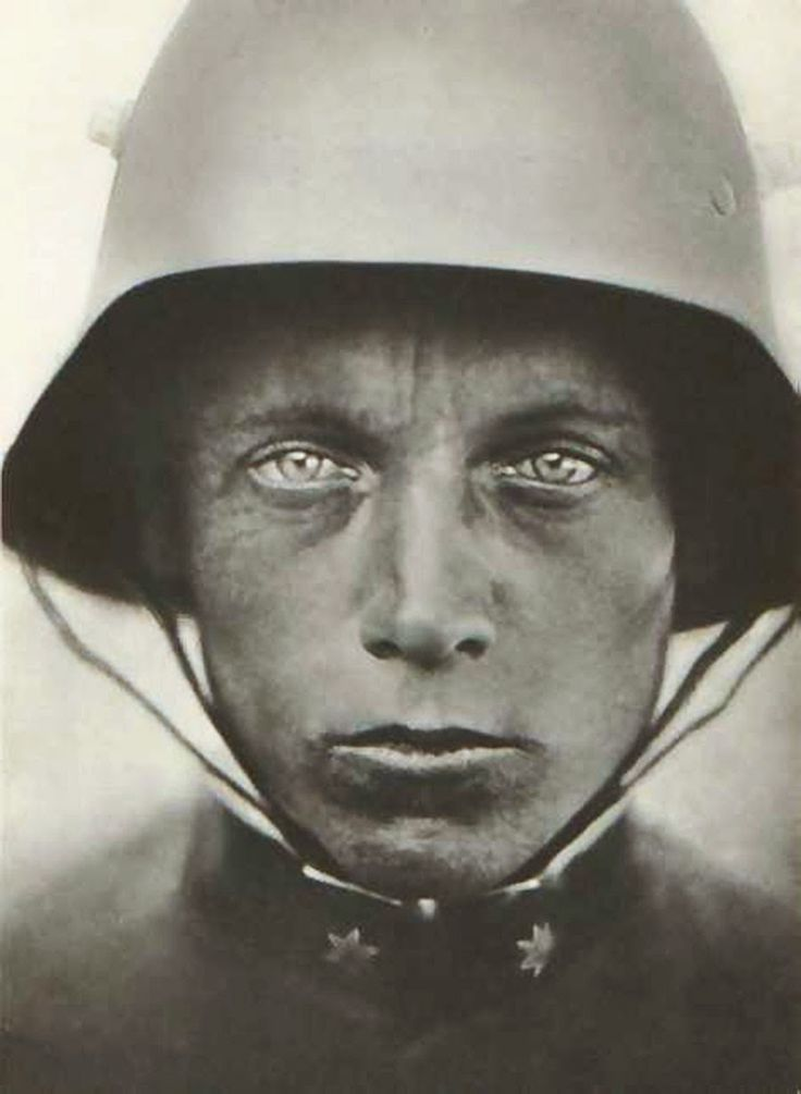 """Austrian-Hungarian soldier, 1918. """"It looks like a thousand yard stare, it's like there's nothing there. The rank insignia indicates that he is Austrian-Hungarian soldier, not German, he's a lance corporal. In case you're wondering, those lugs on the side of his Stahlhelm helmet were combination air vents and mounting lugs for an extra armor plate for nervous soldiers.""""  More information about the Stahlhelm helmet at link."""