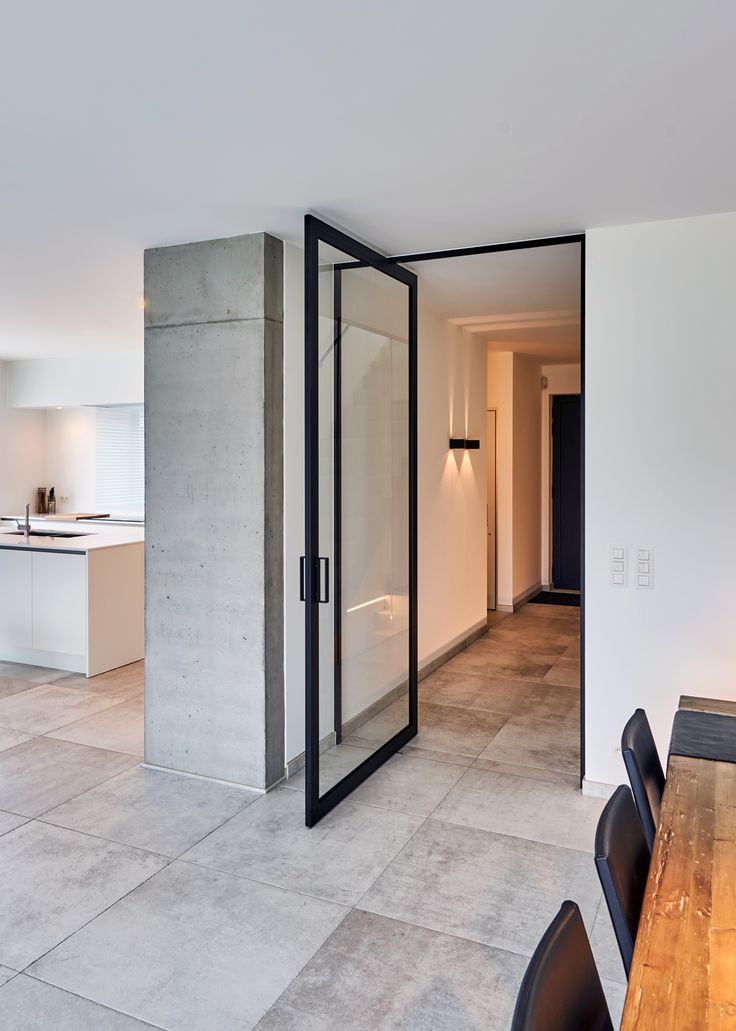Modern glass pivoting door with a black aluminium frame. Custom-made pivot door by Anyway Doors with offset axis pivot hinges without built-in parts to either floor or ceiling. Everything is integrated in the minimalist frame.