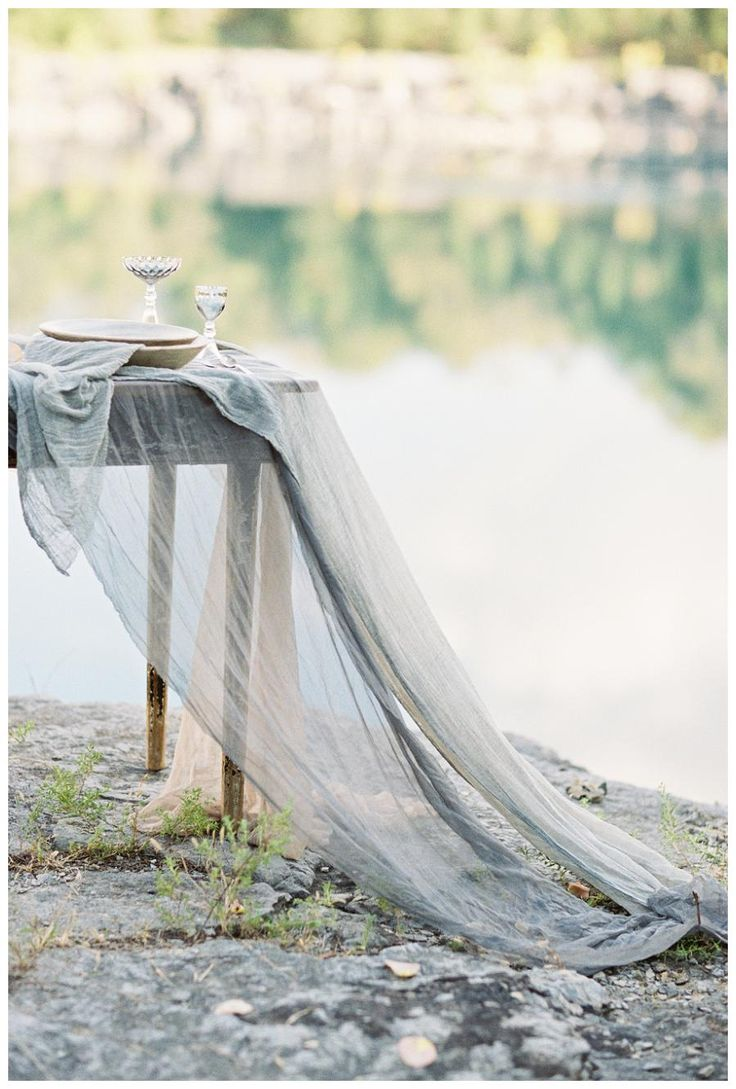Hand dyed silk fabric draping on a rustic outdoor table. Silk by Silk & Willow, image by Sleepy Fox Photography.