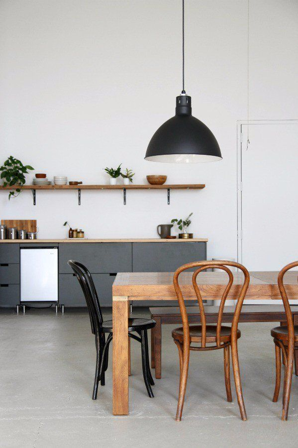 Minimalist open-plan dining space with a farm style wooden dining table, mismatch chairs, a large black pendant light, and gray kitchen cabinents