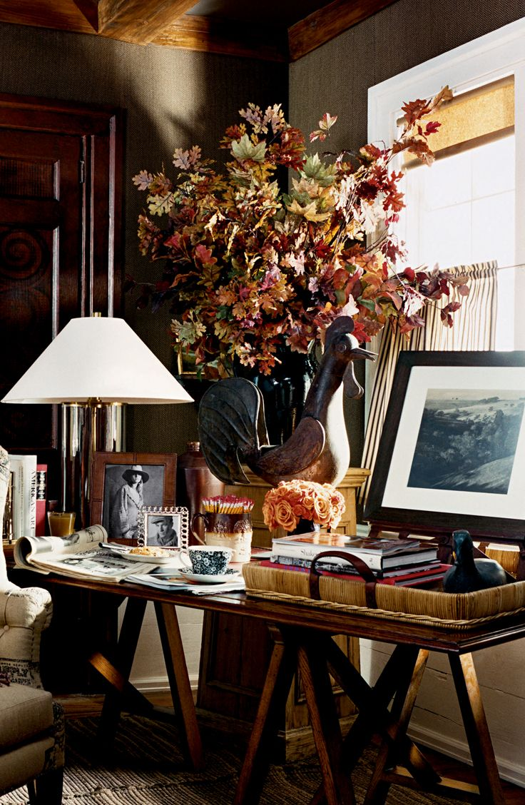Ralph Lauren Home: earth tone florals, fall foliage inspired arrangement is wild and overflowing, near a small prim bouquet of peach roses