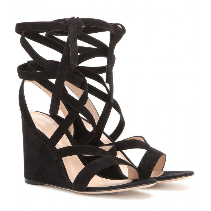 Die Wedge-Sandalen von Gianvito Rossi sind mit ihrer Kombination aus filigranen Riemchen, die sich mehrfach um die Fessel wickeln lassen, und Veloursleder in Schwarz die Essenz von unprätentiöser, sommerlicher Eleganz.