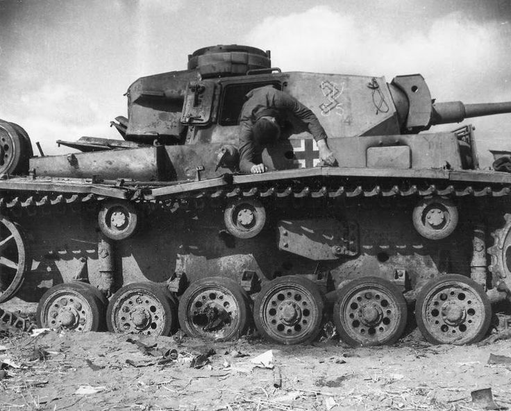 Desert War, 1943: The dead body of a German panzerman of 10.Panzer Division atop his destroyed tank.