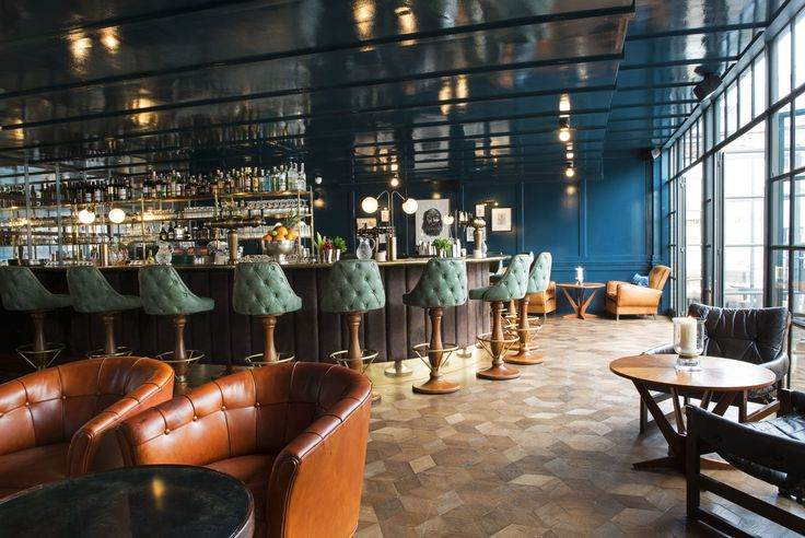 Soft, teal, tufted leather swivel bar stools with gorgeously tapered wooden bases circle the uber-cool bar at The Dean Street Townhouse. Metal studs outline th