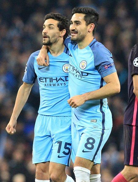 Manchester Citys midfielder lkay Gündogan celebrates their win over Barcelona with team mate Manchester Citys midfielder Jesus Navas after the...