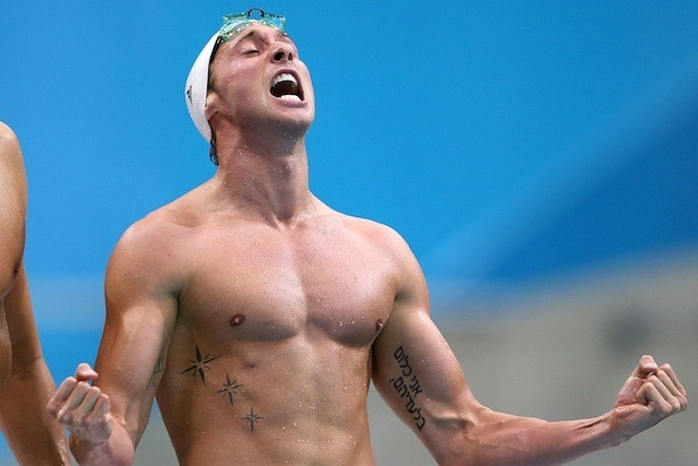 "Fabien Gilot, a swimmer for the French Olympic team at the London 2012 Games, displays an arm tattoo written in Hebrew script. The phrase translates to ""I am nothing without them"" and is dedicated to his Jewish grandfather figure who survived Auschwitz. The gold medal winner displayed the tattoo in reaction to the International Olympic Committee's refusal to observe a minute of silence for the 11 Israeli athletes murdered in a terror attack at the 1972 Munich Olympics."