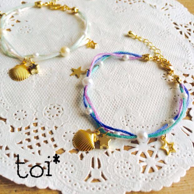 刺繍糸や紐にパールやスター、シェルを通して華奢な印象のブレスレットに。紐を通す穴を微妙に変えてニュアンスを作って。