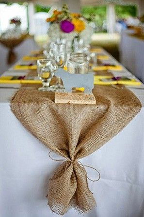 Tying the burlap with a twine bow helps to remove any harsh contrast that the burlap would have against the white table cloth.   See more trending table runners for every wedding here: http://www.mywedding.com/articles/9-trending-table-runners-for-weddings/