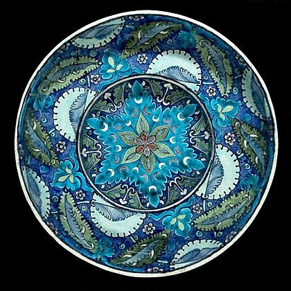 """William de Morgan, Charles Passenger pottery tondino plate. Fulham, circa 1890 the red body covered in white glaze, the inside painted with serrated leaves, split palmettes, knots, flowerheads and crecent moons in shades of blue, turquoise, green and manganese, the outside painted with stylised leaves and bands of turquoise and blue, marked """"Fulham WDM"""" and maker's mark """"CP"""" for Charles Passenger"""