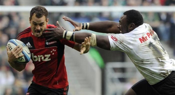 Canterbury Crusaders' Israel Dagg (L) is tackled by South Africa Sharks' Tendai Mtawarira during their Super Rugby round six match at Twickenham, London, March 27, 2011. The Canterbury Crusaders are playing their Super rugby match against Sharks at Twickenham, the home of English rugby, to boost finances and raise money for victims of the Christchurch earthquake.  REUTERS/Paul Hackett