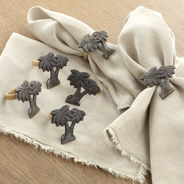 Etched brass with a warm patina gives these napkin rings a laid-back, well-loved look. Fashioned after a pair of swaying palm trees, they add a tropical touch to your tabletop spread. Set of four.
